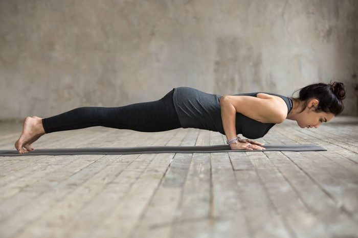Young woman practicing yoga, doing four limbed staff, Push ups or press ups, exercise, chaturanga dandasana pose, working out, wearing sportswear, black pants, top, full length, gray wall in studio