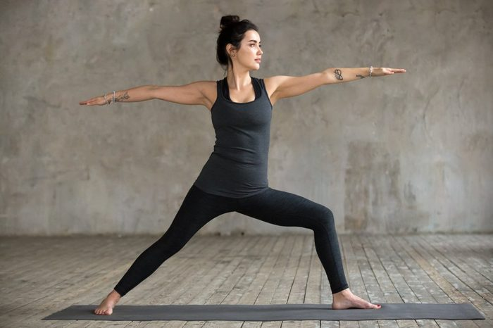 Young woman practicing yoga, doing Virabhadrasana 2 exercise, Warrior Two pose, working out, wearing sportswear, black pants and top, indoor full length, gray wall in yoga studio