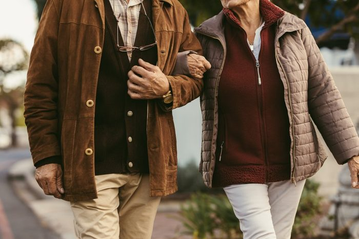 Close up of senior couple holding hands and walking together outdoors. Midsection of old couple walking hand in hand outdoors.