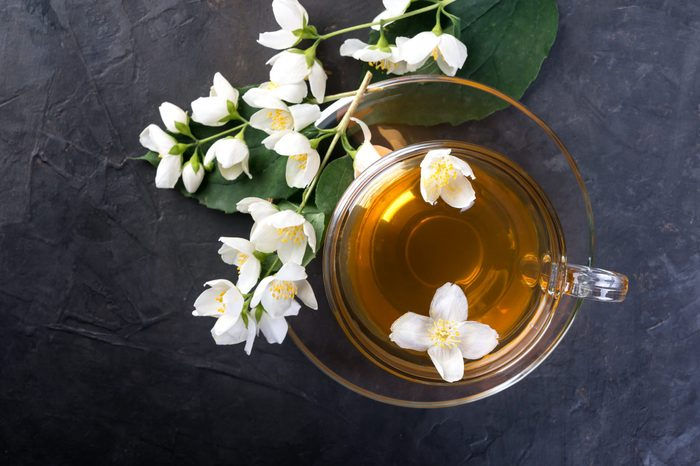 Jasmine tea with jasmine flowers on a dark background, top view