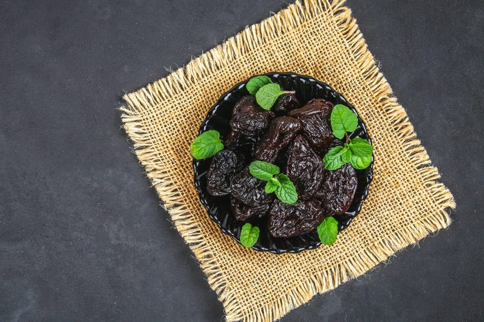 Prunes and fresh mint leaves in a bowl on a concrete table.
