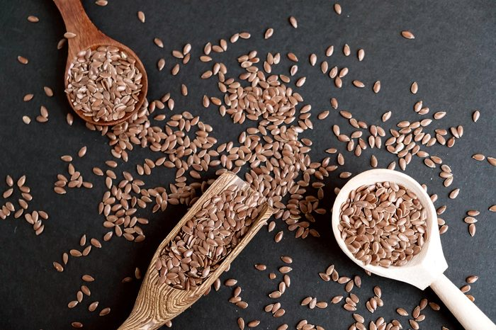 Flax seeds in spoons over dark background. Natural light. Selective focus. Close up on a black background. Top view, flat lay. copy space.