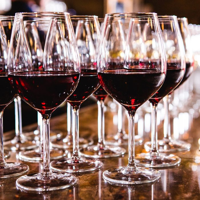 Glasses with red wine on blurred background