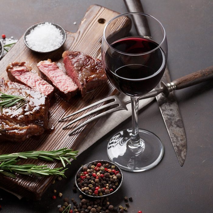 Grilled ribeye beef steak with red wine, herbs and spices on stone table