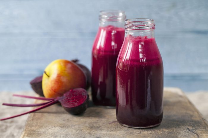 two bottles of beet juice on a cutting board with other fruit