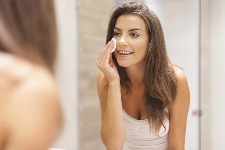 A woman applying a cleansing pad to her skin while standing in front of the mirror.   These skin care ingredients can cause breakouts.