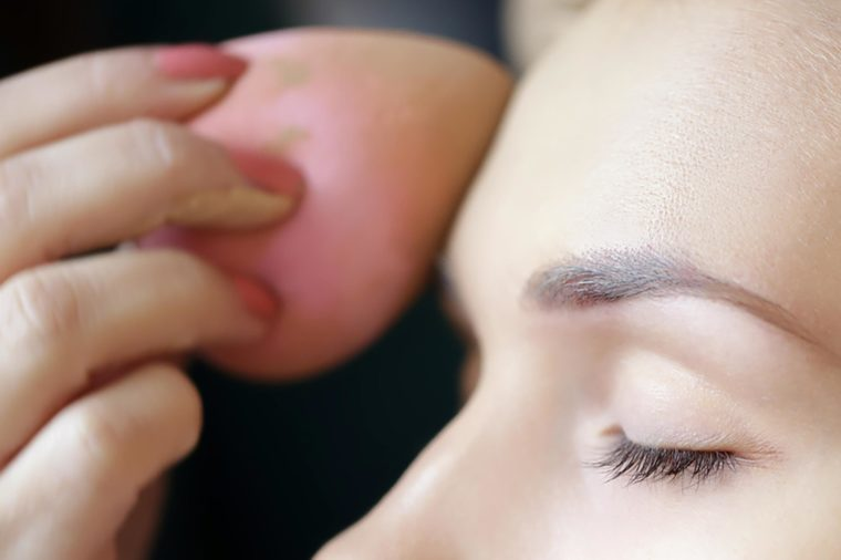 A woman applying foundation to her forehead with a pink beauty blender.   These skin care ingredients can cause breakouts.