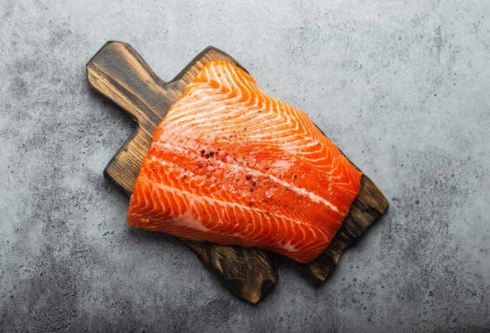 build muscle   fresh raw salmon fillet with seasonings on wooden board, gray stone background. Preparing salmon fillet for cooking, healthy eating concept