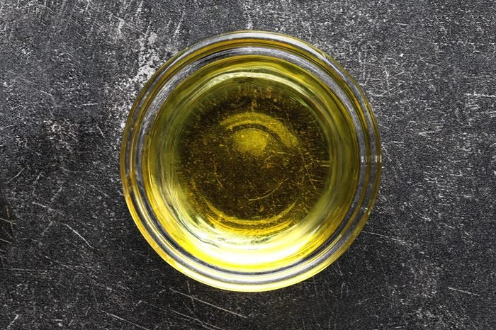Glass bowl with olive oil on dark background
