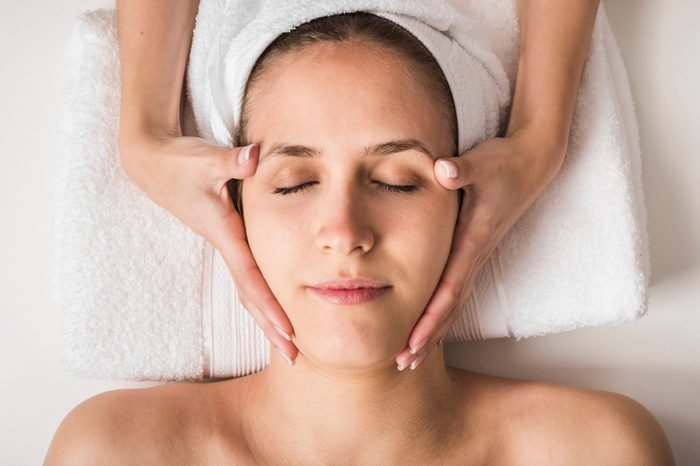 Anti-Aging Treatments   Spa concept. Face massage. Young woman getting spa treatment, close up