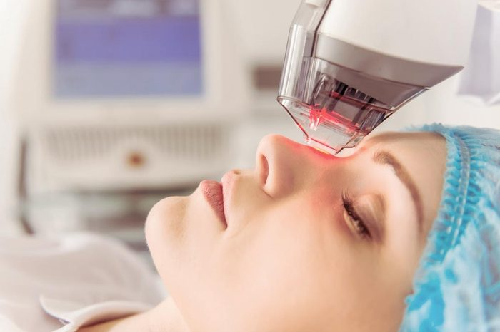 Anti-Aging Treatments   Beautiful female patient is getting a face skin treatment while lying at cosmeticians office, close up