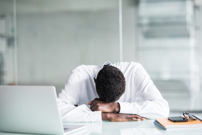 Tired African American employee in formal wear fall asleep after long working hours in office