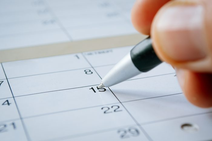 Person writing with a ballpoint pen on a calendar on the date of the 15th with the nib hovering over blank copyspace, oblique angle