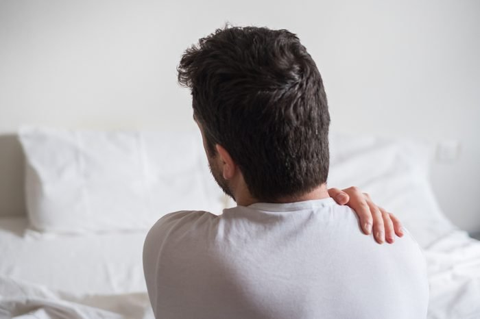 Wake up in the middle of the night | Rear view of one man sitting on bed having back pain
