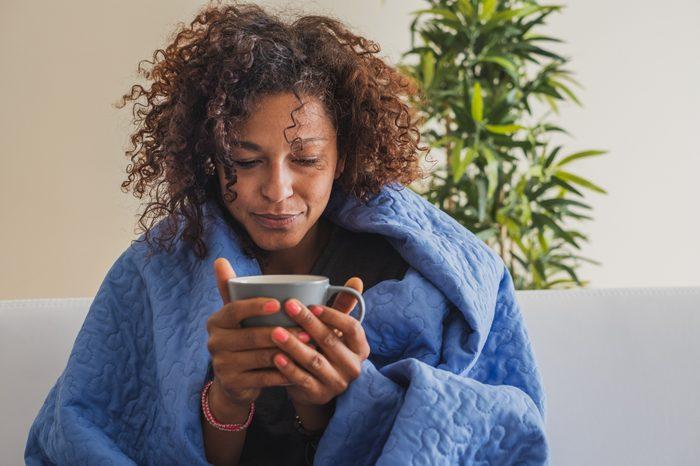 sick woman at home drinking tea