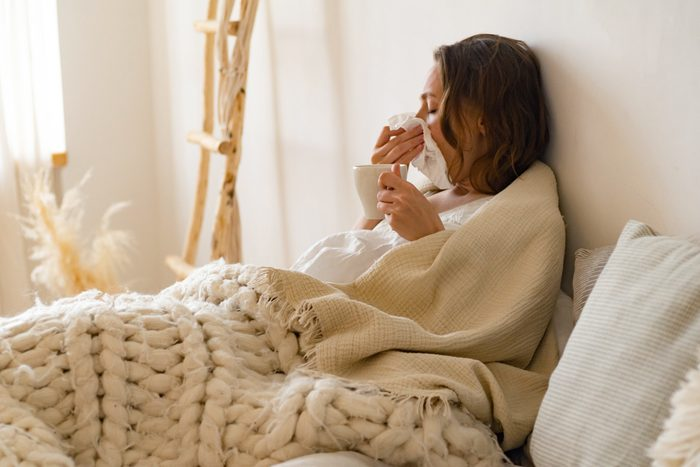 health advice   sick woman blowing her nose
