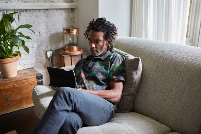 man resting at home using tablet device