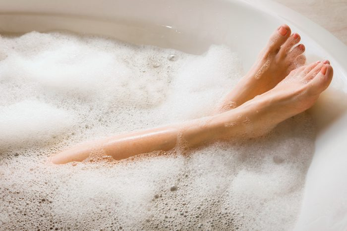 close up of woman's legs in soapy bathtub