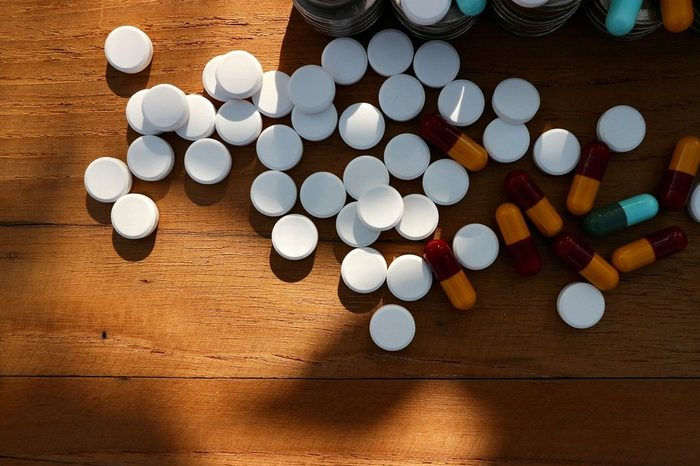 White round pills and capsules with part roll coins money and medicine on wood table in shadow space sunlight