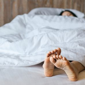Female feet under blanket flat lay. Female beautiful feet on the bed. Sleeping woman legs under white blanket