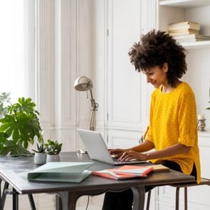woman sitting at desk in home working on laptop