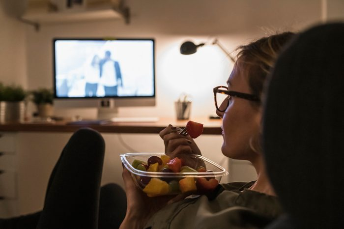 work from home | woman eating a snack and watching a movie at home after work