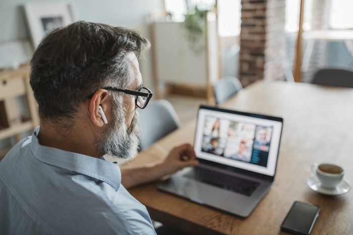 work from home | man on video conference call with coworkers working from home