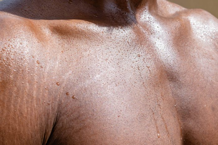 Close up of Black Male sweaty torso with stretchmarks Close up of sweat building up in a African man's body after hard work for summer hear concept