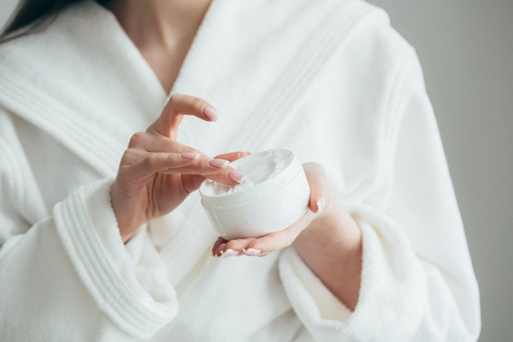 beauty products   Beautiful groomed woman's hands holding a cream jar on the fluffy blanket. Moisturizing cream for clean and soft skin in winter time. Manicure beauty salon. Healthcare concept. Spa