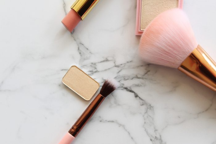 shouldn't be stored in the bathroom | Gold and pink makeup objects against white marble copy space.