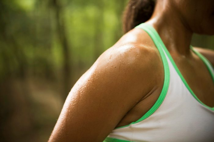 cause dehydration   close up of woman's sweaty shoulder outside during exercise