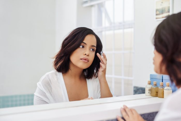 skin says about your health | woman looking at face in mirror