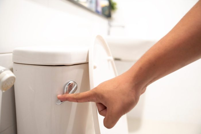 cause hemorrhoids   close up of hand flushing toilet