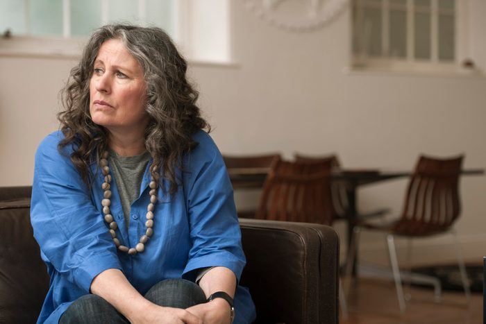 upset and worried woman sitting on couch