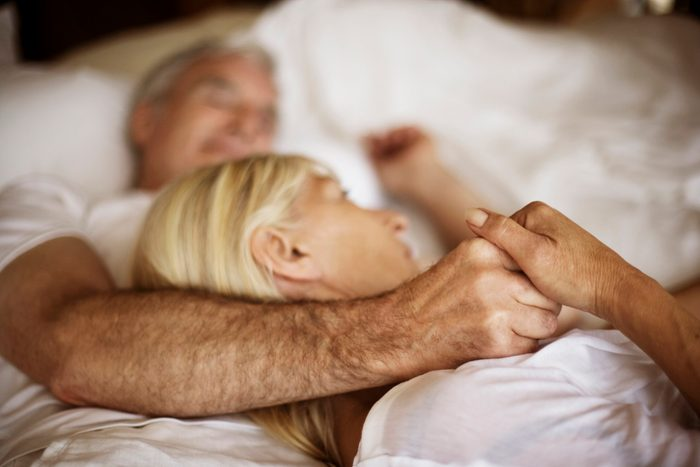 close-up of couple holding hands in bed