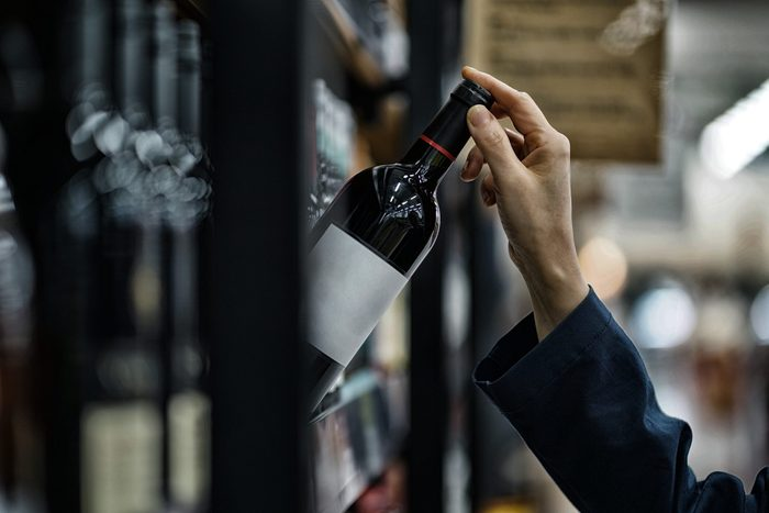 close up of woman's hand taking wine off store shelf