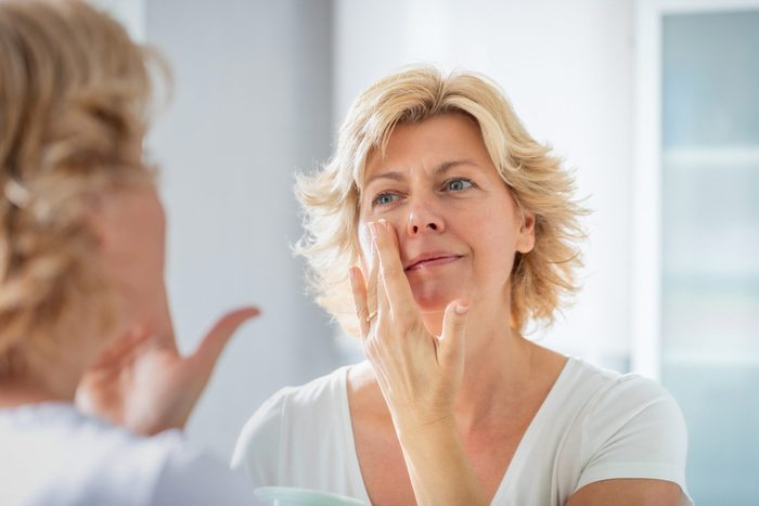 phymatous rosacea | woman looking in the mirror and touching face