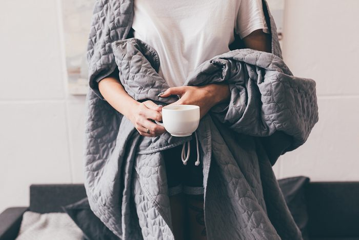 weighted blankets benefits   woman holding a blanket around her body   weighted blankets anxiety