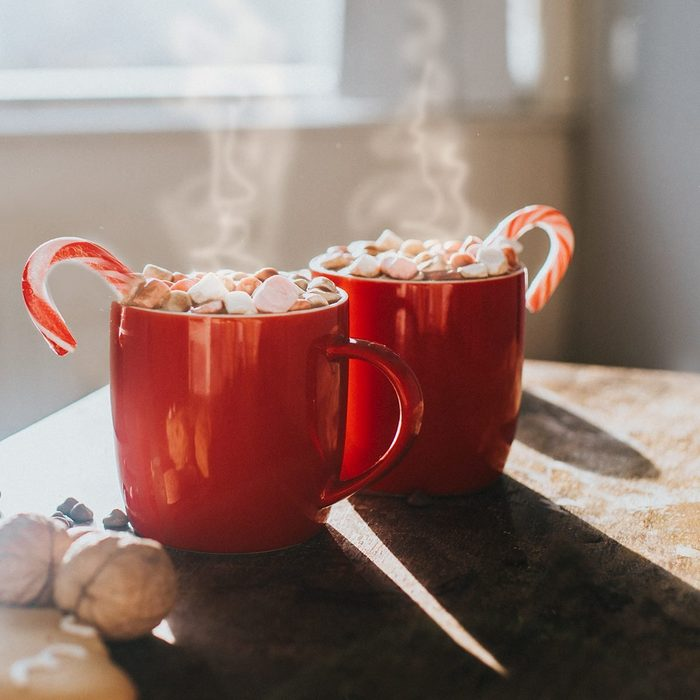 Two red mugs of hot chocolate, with marshmallows and candy canes in a sunny daytime environment.