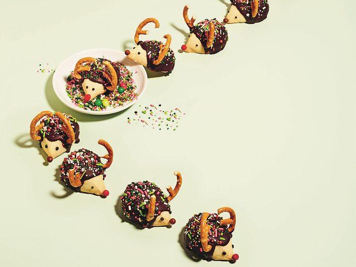 kim-joy christmas cookies | little hedgehog cookies arranged to look like they're marching through sprinkles