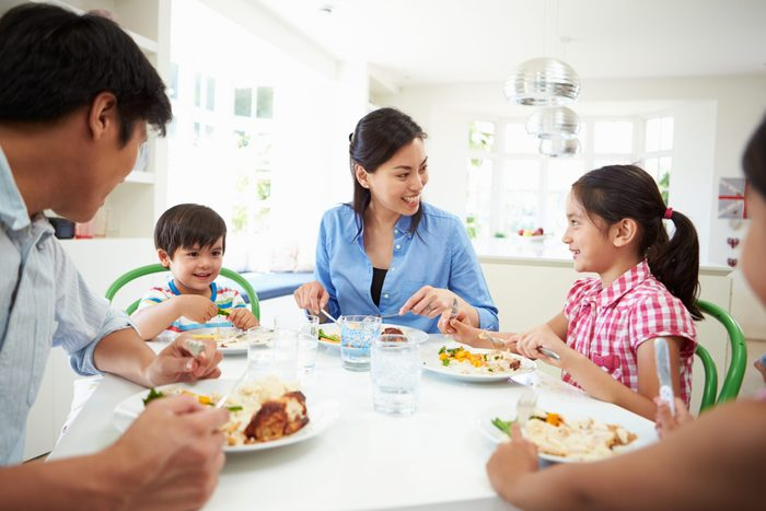 children healthy relationship with food   family talking and eating around a dinner table