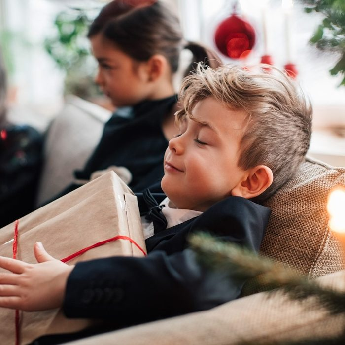 Smiling boy holding Christmas present while sitting with family in living room