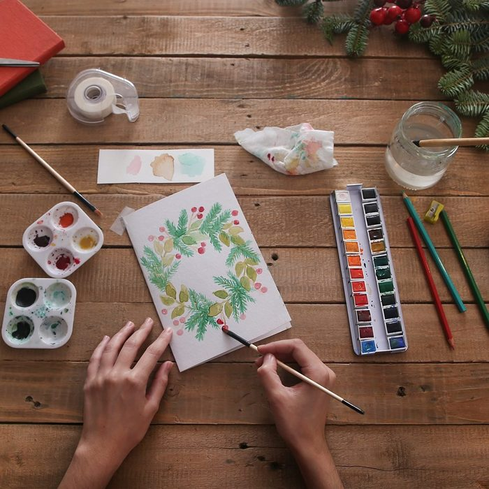 Young woman painting Christmas card with water colors, top view