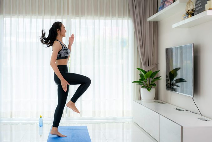 cardio workouts at home   Asian Woman Doing Strength Training Cardio Aerobic Dance Exercises U201chigh Kneeu201d While Watching Videos Fitness Workout Class Live Streaming Online On A Smart Tv In The Living Room At Home