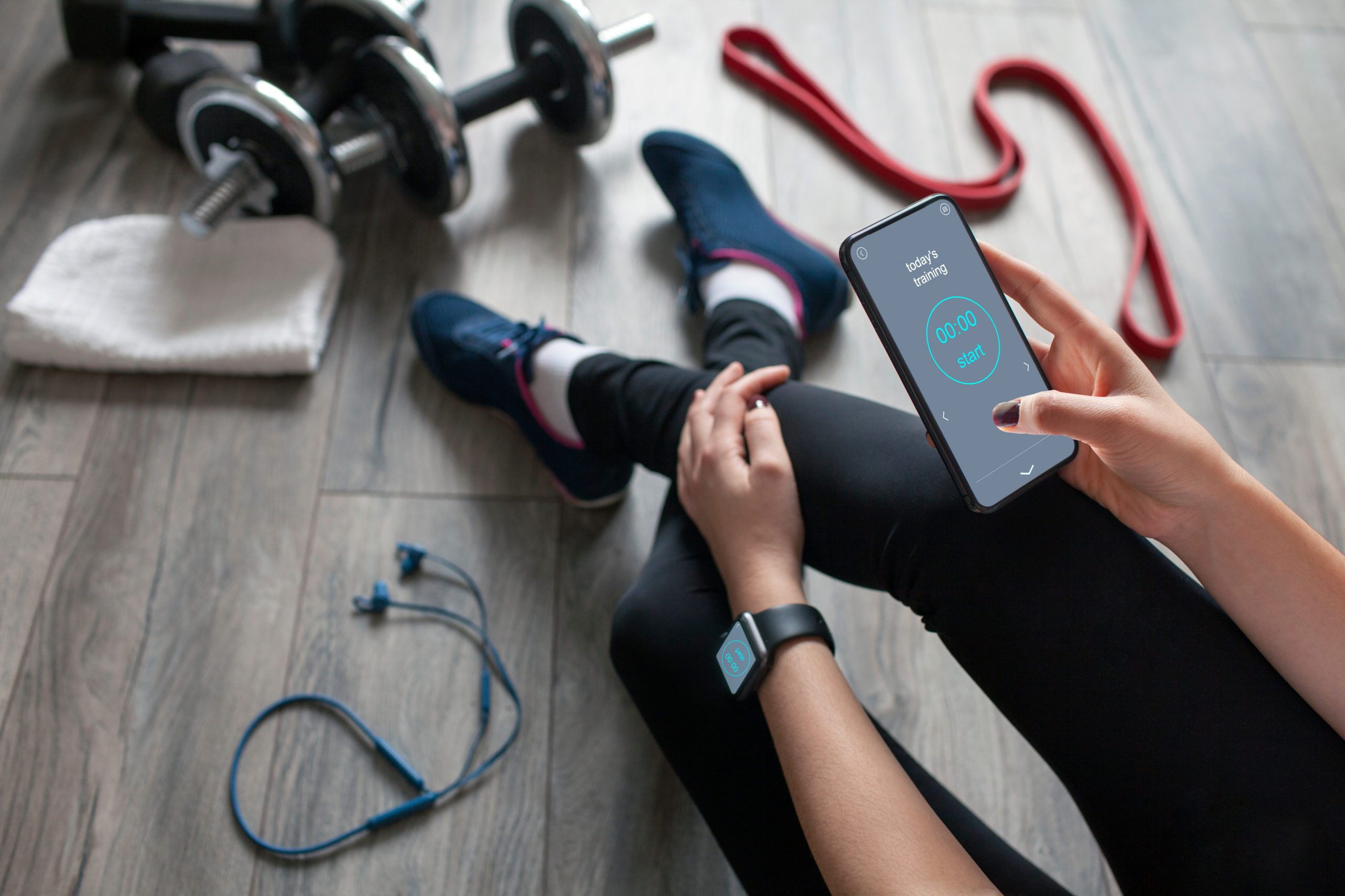 best fitness app   woman sitting and scrolling through their fitness app