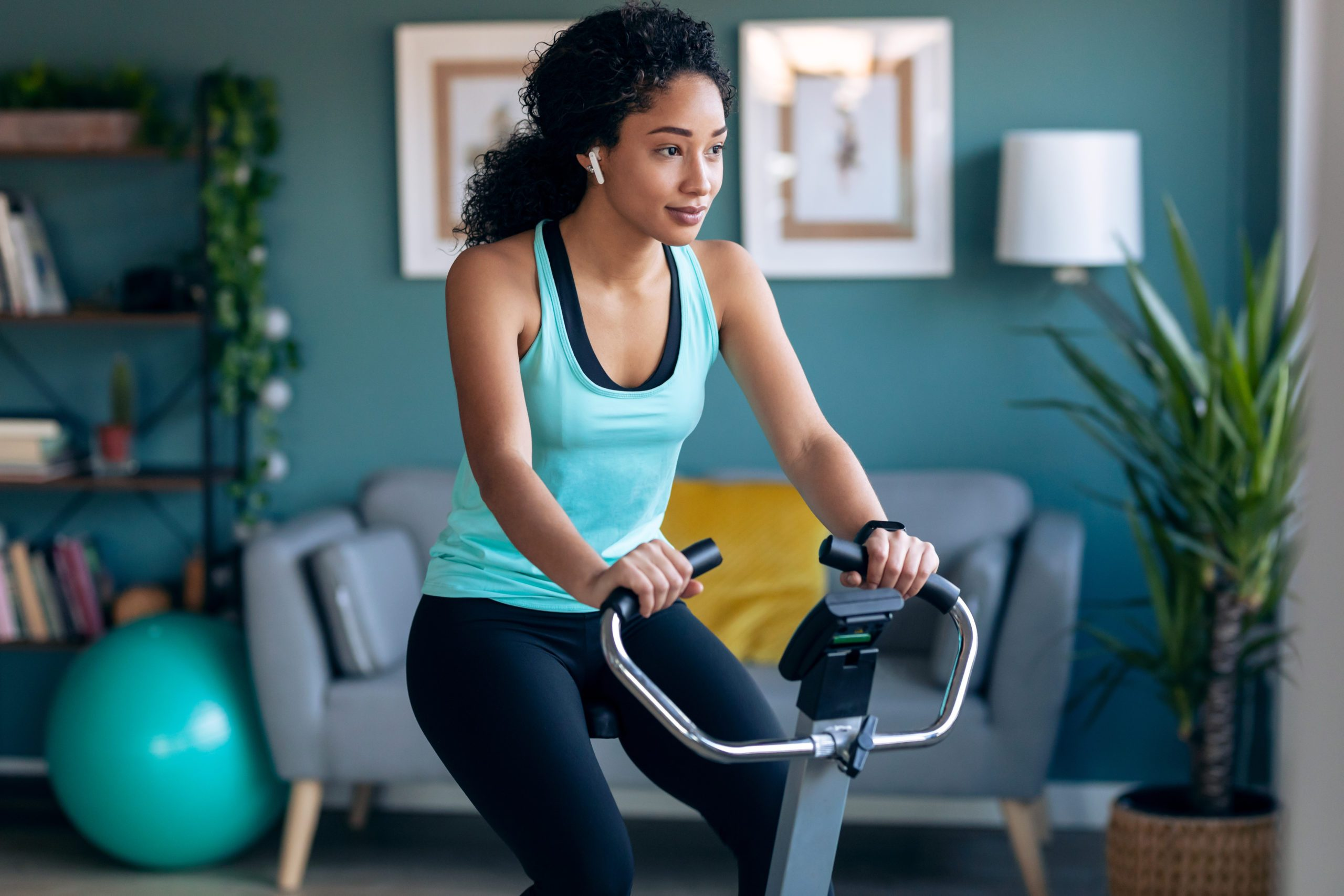 Shot,of,sporty,african,young,woman,exercising,on,smart,stationary