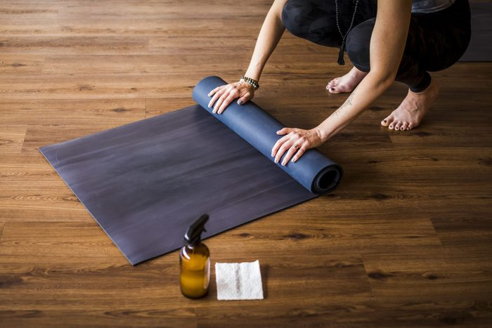 Woman Rolling Up Yoga Mat With Sanitizer Nearby