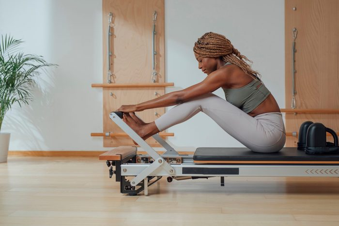 Woman Doing Pilates Exercise On Reformer
