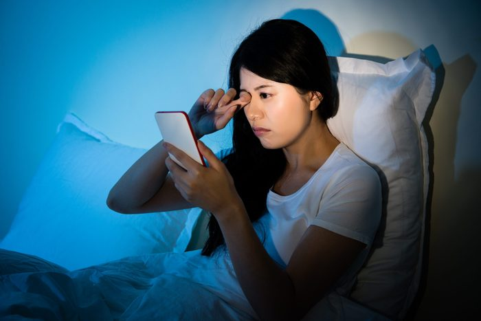 revenge bedtime procrastination  Woman,rubbing,her,eyes,feel,painful,with,using,smartphone,sitting