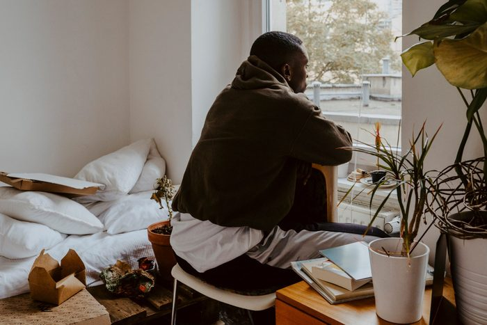 post-pandemic   anxiety after covid-19Rear View Man Looking Through Window While Sitting In Bedroom